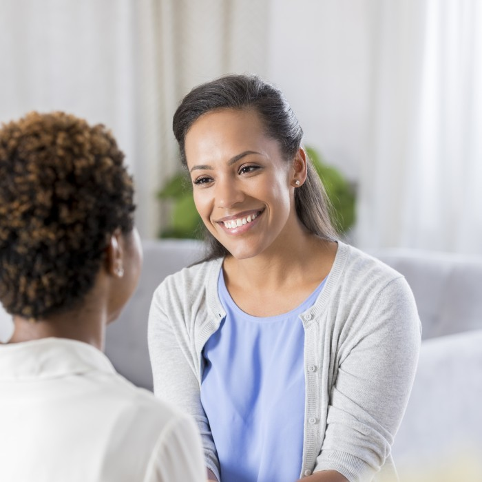 health professional warmly greets a new patient in her office.
